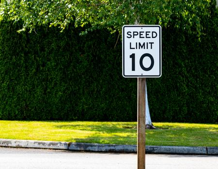 Foto de Ten mile per hour speed limit sign with green bushes and tree - Imagen libre de derechos