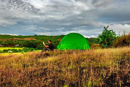 man reading book while camping at mountain top at evening image is taken at gokarna karnataka india. it is showing the human love towards the nature and book reading.