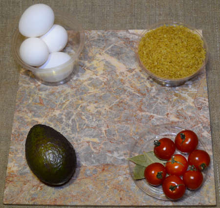 ingredients for instant cooking of an interesting dish: eggs, bulgur, avocado, cherry tomatoes, bay leaf