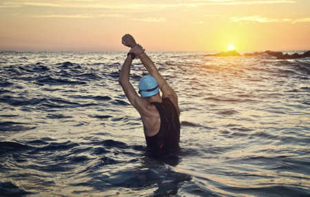 Photo pour young athlete triathlon in front of a sunrise over the sea - image libre de droit