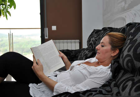 woman reading on the sofa quietly in a autumn day