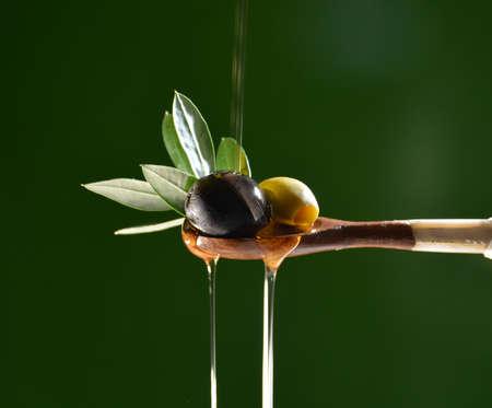 Foto de Olive oil falling on two olive with olive leaves to flavor a Mediterranean salad . Typical dish of the Mediterranean diet - Imagen libre de derechos