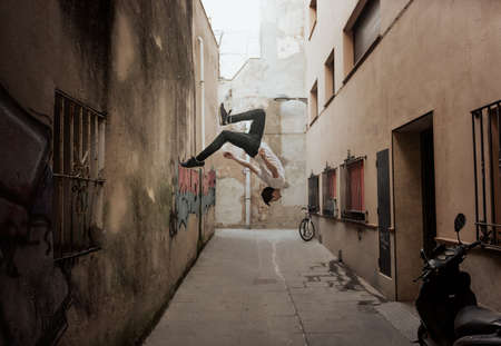 Photo for young sportsman practicing parkour, acrobatics and deadly jumps in the streets of the city - Royalty Free Image
