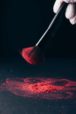 Photo for Make-up brush with violet powder explosion on black - Royalty Free Image