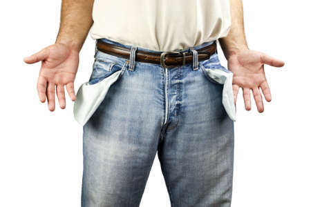 Young unemployed man dressed in blue denim jeans showing empty pockets isolated on white background with copy space