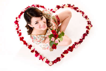 young woman with roses sitting inside a heart shaped made of rose petals