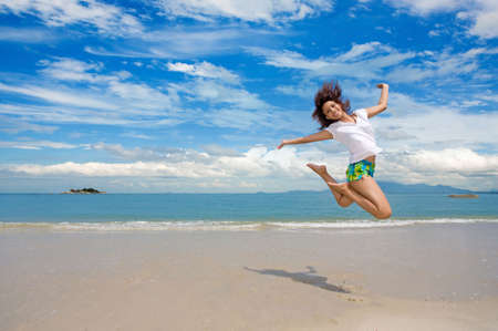Photo for young beautiful girl jumping gracefully at the beach - Royalty Free Image