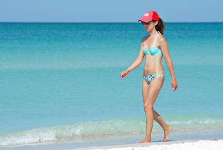 Photo for HOLMES BEACH, ANNA MARIA ISLAND, FL / USA - May 1, 2018: Beautiful Young Woman taking a leisure walk on the Beach enjoying a Beautiful Summer Day. - Royalty Free Image
