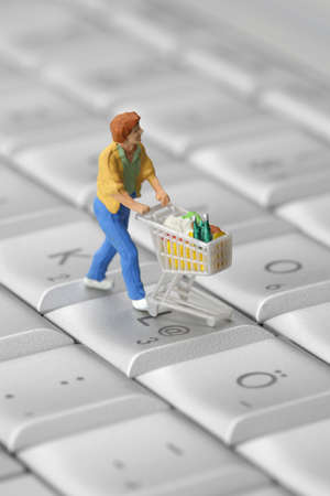 Miniature shopper with shopping cart on a computer keyboard. Online shopping concept.