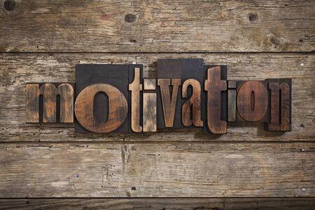 motivation, single word set with vintage letterpress printing blocks on rustic wooden background
