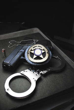 Tools of the trade in Law Enforcement, badge, handcuffs, and firearm/Protect & Serve