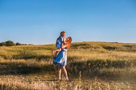 Photo pour Young mother and daughter have fun and playing in a golden field of sunshine while on a summer holiday. Family activities and outdoors concept. - image libre de droit