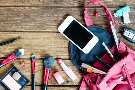 Photo pour Top view of women bag stuff female cosmetic accessories on wooden texture background - image libre de droit