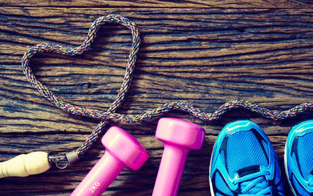 Foto de Fitness workout love concept - Top view of sport shoes, dumbbells and jump rope in heart shape on wooden background - Imagen libre de derechos