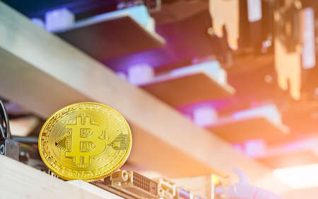 Bitcoin Cryptocurrency background concept - Golden bitcoin with a computer graphic card or GPU rig cryptocurrency mining unit in background