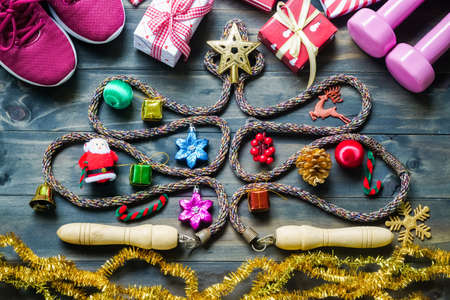 Photo pour Fitness, healthy and active lifestyles greeting card concept, dumbbells, sport shoes, skipping rope or jump rope  in the form of christmas tree with Christmas decoration on wood background retro tone. Exercise, Fitness and Working Out Merry Christmas and Happy new year concept. - image libre de droit