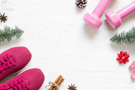 Foto de Flat lay of Merry Christmas and Happy new year for healthy and active lifestyle concepts. Composition with dumbbells, sport shoes and Christmast decoration on grunge white wood background. - Imagen libre de derechos