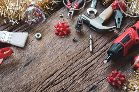 Photo pour Merry Christmas and Happy New Years Handy Constrcution Tools background concept.  Handy House Fix DIY handy tools with Christmas ornament decoration on a rustic wooden table. - image libre de droit