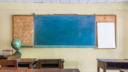 Photo pour Vintage retro classroom interior with empty chalkboard for your copy space. Education and school background concept. Blank blue chalkboard in front of  school class with wooden student desks and chairs - image libre de droit