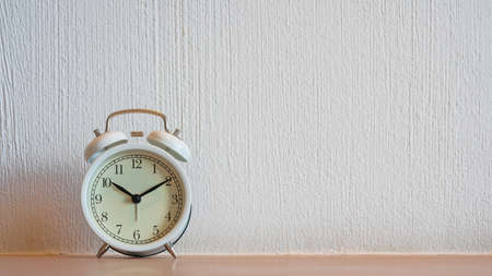 Photo pour White vintage alarm clock displaying 10:10 am or pm on wooden table and white wall background. - image libre de droit