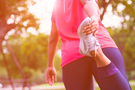 Foto de Sport woman stretching leg muscle preparing for running in the public park outdoor. Close up of female athlete lower body doing legs stretches getting ready for cardio warmup. - Imagen libre de derechos