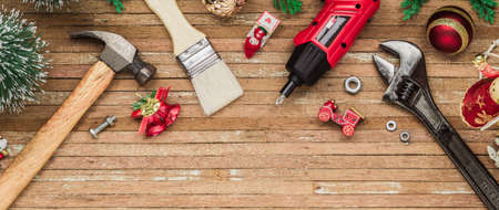 Photo for Merry Christmas and Happy New Years Handy Constrcution Tools web banner background concept. Handy House Fix DIY handy tools with Christmas ornament decoration on a rustic wooden table. - Royalty Free Image