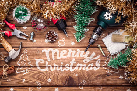 Photo for Merry Christmas and Happy New Years Handy Construction Tools background concept. Handy House Fix DIY handy tools with Christmas ornament decoration on a rustic wooden table. Industrial Xmas Background. - Royalty Free Image