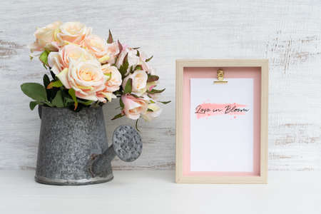 Photo for Mockup Still life Picture frame and at watering can with Bouquet of roses on grunge white wood. Valentines Day Background concept. Mock up with photo frame for your picture or text - Royalty Free Image