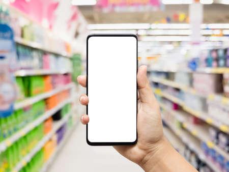 Foto für Hand holding smartphone with blurred supermarket - Lizenzfreies Bild
