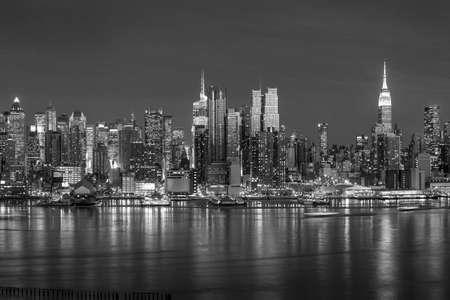 New York City with skyscrapers illuminated over Hudson River panorama in black and white