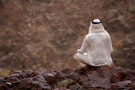 Photo pour A view of a young Arab man sitting on a rocky overlook. - image libre de droit