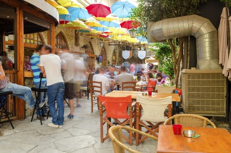 Stoa Fylaktou in the historic medieval city center of Limassol in Cyprus. A view of the cafe, restaurant, the colorful umbrellas hang over the tables and the old decorated walls.