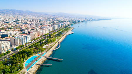 Photo for Aerial view of Molos Promenade park on the coast of Limassol city centre in Cyprus. Bird's eye view of the jetties, beachfront walk path, palm trees, Mediterranean sea, piers, rocks, urban skyline and port from above. - Royalty Free Image