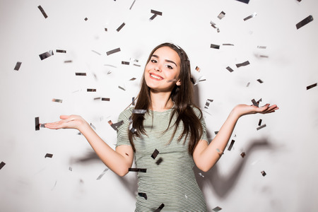 Photo for happy young woman or teen girl in fancy dress with sequins and confetti at party on grey background - Royalty Free Image