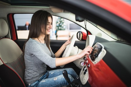 Photo for Car dashboard. Radio closeup. Woman sets up radio - Royalty Free Image