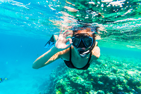 Woman underwater snorkeling with victory happy sign swimming in sea