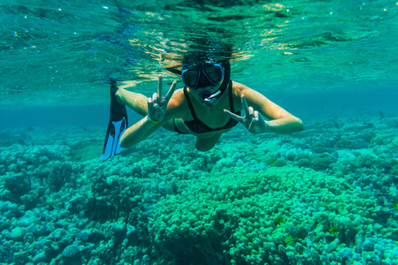 Woman underwater snorkeling with victory sign swimming in sea