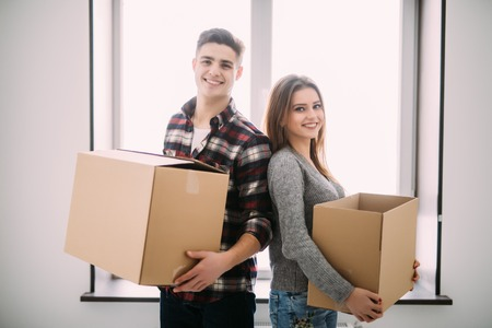 Couple with boxes moving into new home smiling