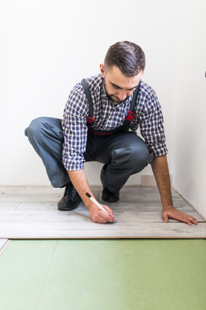 Male worker installing laminate flooring, man installing new wooden laminate flooring, man laying laminate flooring at home, carpenter worker installing laminate flooring in the room