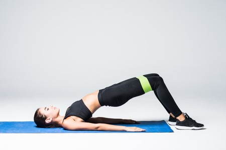 Foto de Woman exercising doing workout for legs with elastic bands lying on floor on white background - Imagen libre de derechos