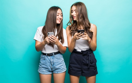 Two multiethnic women both using cell phones isolated over blue background