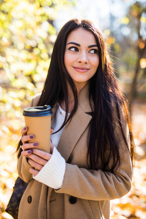 Photo pour Young woman walking in the autumn city street and drinking take away coffee in paper cup. - image libre de droit
