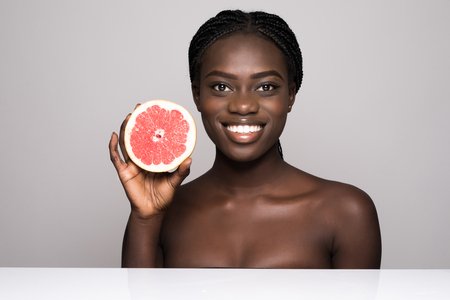 Foto de Beauty african woman with orange citrus grapefruit with healthy skin body. Attractive fresh vitamin. Studio shot. - Imagen libre de derechos