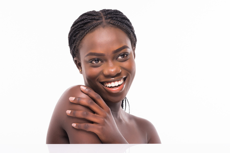 Foto de Close up beauty portrait of african beautiful half naked woman applying face cream and looking away isolated over white background - Imagen libre de derechos