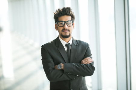Foto per Portrait of young businessman with glasses in suit with crossed hands near window in modern office. - Immagine Royalty Free