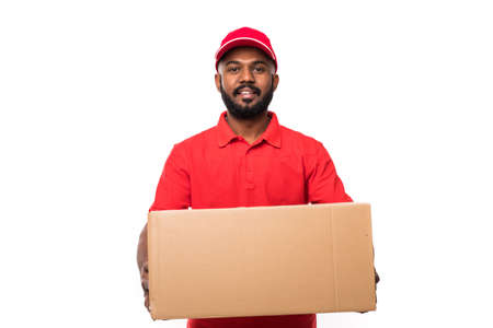 Photo for Side view of young delivery man with box. isolated gray background - Royalty Free Image