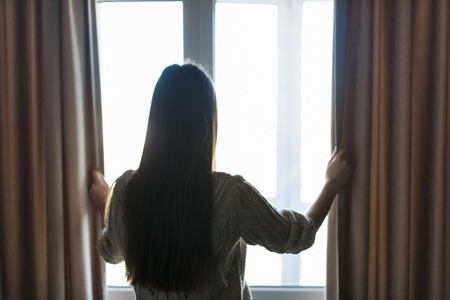 Photo for Rear view - young fit woman in home clothes opens curtains of bedroom window. Young girl is ready for new plans and new challenges. - Royalty Free Image