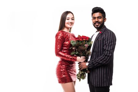 Photo pour Beautiful romantic couple in love isolated on grey background. Attractive young woman holding red roses while hugging her handsome man. - image libre de droit