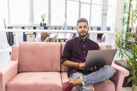 Photo for Casual young man using laptop with happy on sofa in modern office, process color. - Royalty Free Image