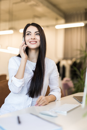 Photo for Portrait of a smiling dark hair businesswoman sitting at a white desk in a luminous office She is wearing a black suit jacket talking on the phone touching some corporate papers her laptop next to her. - Royalty Free Image